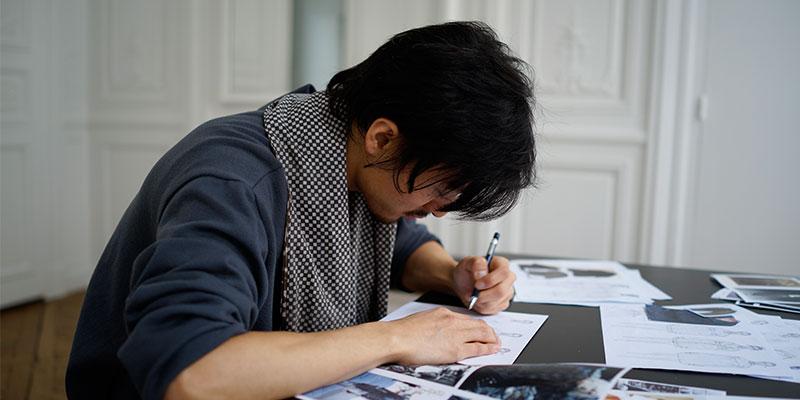 デザイン画を描く豊嶋さん。様々な資料を元にアイデアを膨らませていく。