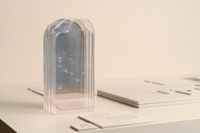 俳人の福田若之さんとデザイナーの梶原恵さん・矢崎花さんによる作品『「日が亘(わた)り樹氷の景が組みあがる」」。アクリル板のレイヤーに文字がばらばらに配置されており、正面から見ると一句が読める